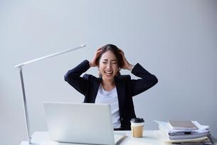 職場のデスクで頭を抱える女性の写真素材 [FYI01464446]