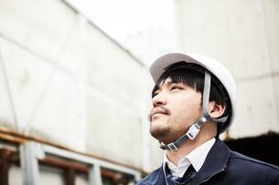 上を見上げている作業服とヘルメットの男性の写真素材 [FYI01464448]