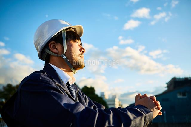 遠くを見ている作業服とヘルメットの男性の写真素材 [FYI01464451]