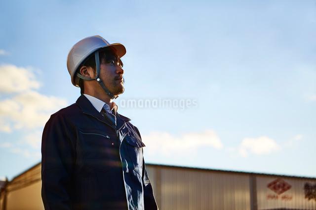 遠くを見ている作業服とヘルメットの男性の写真素材 [FYI01464452]