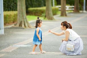 木が立ち並んだ道でしゃがんだ母と会話をする娘の写真素材 [FYI01464457]