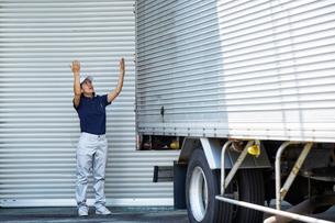 大きなトラックを誘導する働く女性の写真素材 [FYI01464467]