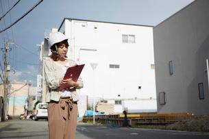 ヘルメットを被り書類を持ちながら点検をする女性の写真素材 [FYI01464473]