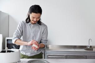 キッチンでおにぎりを握る男性の写真素材 [FYI01464475]