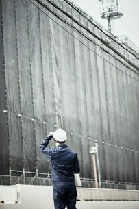 工事中の建物を見ている作業服とヘルメットの男性の写真素材 [FYI01464476]