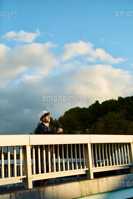 橋の上から遠くを見ている作業服とヘルメットの男性の写真素材 [FYI01464481]