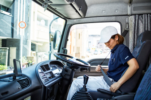 トラックに乗ってシートベルトを閉める女性の写真素材 [FYI01464496]