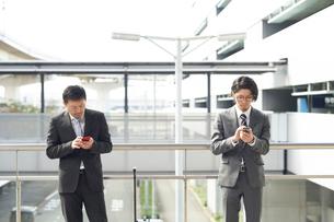スマートフォンを確認するサラリーマンの写真素材 [FYI01464500]