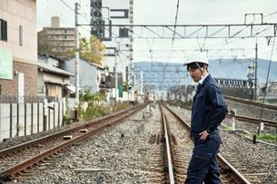線路を渡る作業服とヘルメットの男性の写真素材 [FYI01464522]