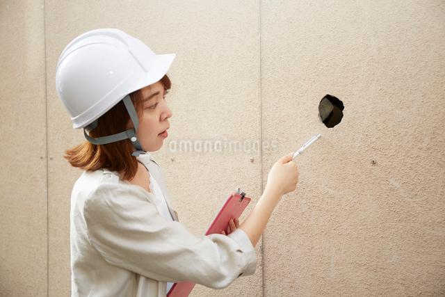 ヘルメットを被り書類を持ちながら点検をする女性の写真素材 [FYI01464524]