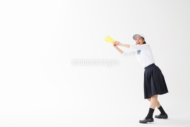 メガホンをバットのように持つ帽子をかぶった女子高生の写真素材 [FYI01464525]