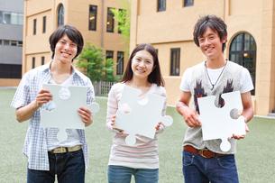 パズルピースを持つ3人の大学生の写真素材 [FYI01464541]