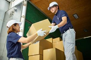 トラックから段ボール箱を積み降ろす作業服の男女の写真素材 [FYI01464549]