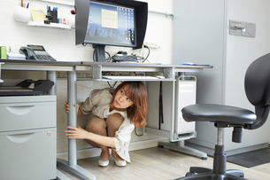 オフィスの机の下に隠れる女性の写真素材 [FYI01464554]