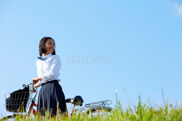 自転車を押して歩く女子高生の写真素材 [FYI01464558]