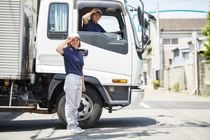 トラックに乗っている男性と横に立っている女性の写真素材 [FYI01464564]