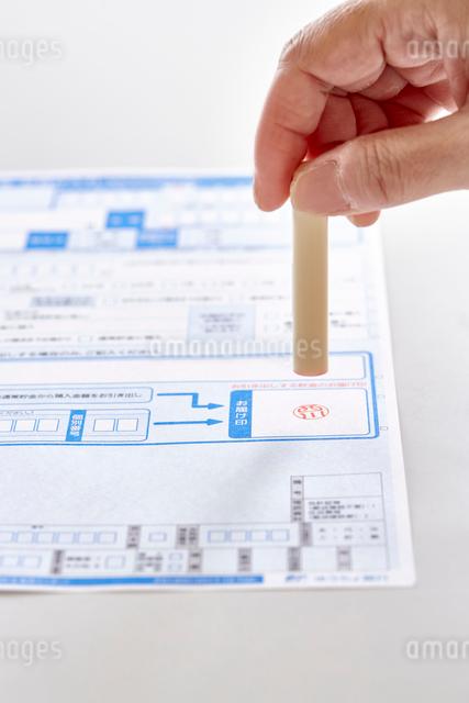 書類と印鑑を持つ女性の手元の写真素材 [FYI01464566]