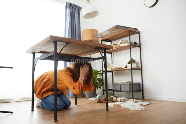 自宅にいるときに地震がきて怯える女性の写真素材 [FYI01464573]