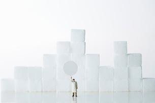 角砂糖の前に立つ白衣を着たミニチュア人形の写真素材 [FYI01464577]