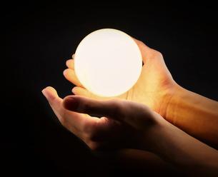 光る電球と男性の手の写真素材 [FYI01464593]