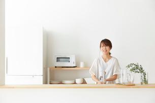 シンプルでナチュラルなオープンキッチンで微笑む女性の写真素材 [FYI01464602]