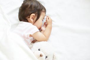 クマのぬいぐるみと一緒に眠る赤ちゃんの写真素材 [FYI01464614]