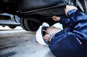 車の下に潜り込み作業をする作業服とヘルメットの男性の写真素材 [FYI01464622]