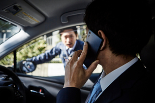車の中で電話をかける男性とその様子を見ている外の男性の写真素材 [FYI01464625]