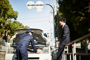 ボンネットを開けて中の様子を見ている作業服の男性の写真素材 [FYI01464627]