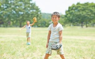 公園の芝生で野球をする兄弟の写真素材 [FYI01464658]