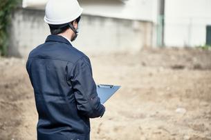 空地を前に立つ作業服とヘルメットの男性の写真素材 [FYI01464670]