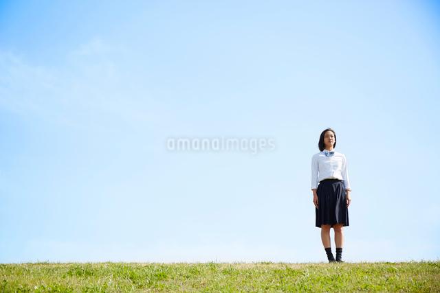 河川敷に立って遠くを見つめる女子高生の写真素材 [FYI01464672]