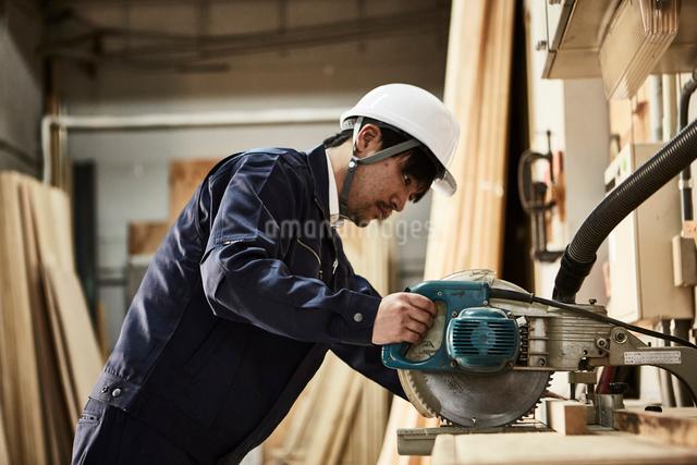電動のこぎりを使う作業服とヘルメットの男性の写真素材 [FYI01464684]