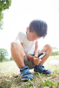 虫メガネで地面を観る真剣な顔の男の子の写真素材 [FYI01464693]
