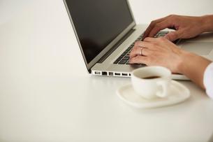 白いテーブルでパソコンをする男性の手元元の写真素材 [FYI01464696]
