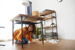 自宅にいるときに地震がきて怯える女性の写真素材 [FYI01464704]