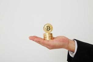 たくさんのビットコインを持った手の写真素材 [FYI01464709]
