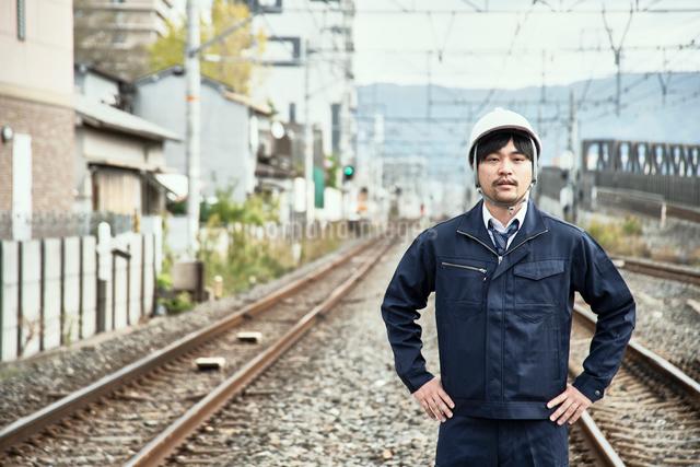 線路をバックに立つ作業服とヘルメットの男性の写真素材 [FYI01464720]
