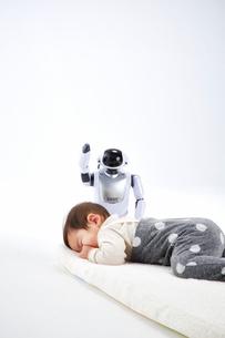 お昼寝する赤ちゃんを見守るロボットの写真素材 [FYI01464723]