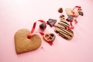 ピンクの背景に並んだクッキーとチョコレートの写真素材 [FYI01464727]