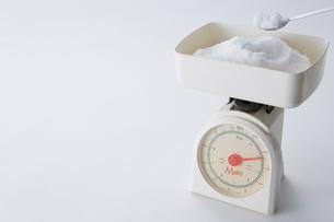 白い背景に置いてある砂糖がのった計りの写真素材 [FYI01464729]