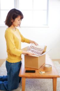 畳んだセーターを箱に詰める女性の写真素材 [FYI01464737]