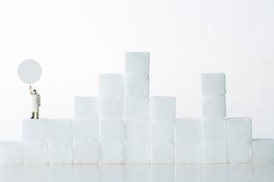 角砂糖の山の上に立つ白衣を着たミニチュア人形の写真素材 [FYI01464742]