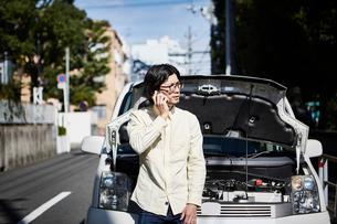 ボンネットを開けた車の前で電話をかける男性の写真素材 [FYI01464746]
