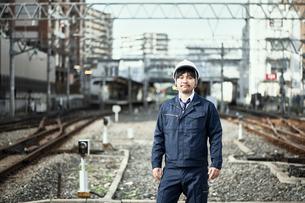 線路に立つ作業服とヘルメットの男性の写真素材 [FYI01464764]