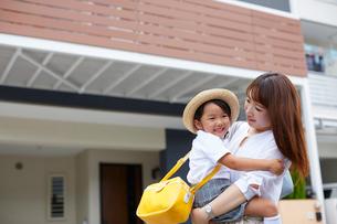 家の前で子供を抱っこする母親の写真素材 [FYI01464783]