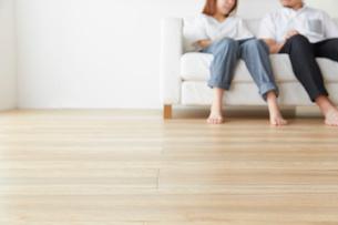 シンプルな部屋で白いソファに座って話す男女の写真素材 [FYI01464788]
