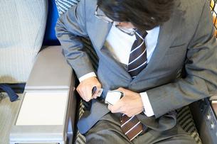 飛行機でシートベルトを装着するサラリーマンの写真素材 [FYI01464798]
