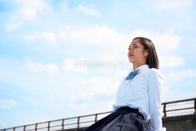 土手で足を伸ばして座る女子高生の写真素材 [FYI01464801]