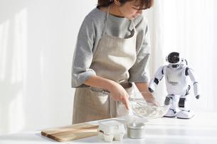 ロボットとお菓子作りをしている女性の写真素材 [FYI01464803]
